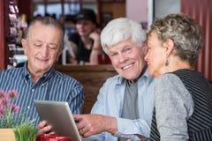 Tre pensionärer som använder minnestavladatoren i bistroer Arkivbild