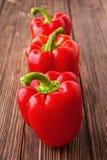Tre peperoni dolci rossi su un fondo di legno Fotografia Stock Libera da Diritti