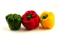 Tre peperoni dolci in una riga su bianco Immagine Stock