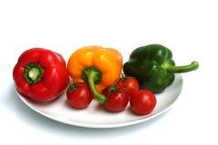 Tre peperoni ed alcuni pomodori Fotografia Stock