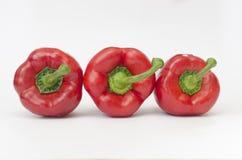 Tre peperoni su una priorità bassa bianca Immagini Stock
