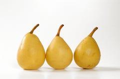 Tre pere gialle in una fila con fondo bianco Fotografia Stock