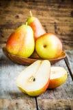 Tre pere organiche mature fresche e quella affettata Fotografia Stock