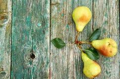 Tre pere verdi con le foglie su marrone verde di legno hanno invecchiato la fine del fondo di struttura su con lo spazio della co Immagini Stock