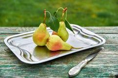 Tre pere verdi con le foglie sul piatto d'annata grigio con il coltello d'argento su marrone verde di legno hanno invecchiato la  Fotografie Stock
