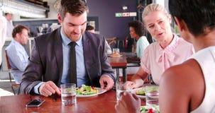 Tre persone di affari che hanno colazione di lavoro in ristorante archivi video