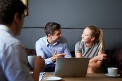Tre persone di affari che hanno riunione in caffè Fotografie Stock