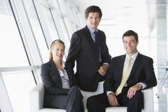 Tre persone di affari che si siedono nell'ingresso dell'ufficio fotografie stock libere da diritti
