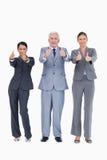 Tre persone di affari sorridenti che danno i pollici su Fotografie Stock Libere da Diritti
