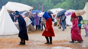 Tre personer går under regnet Arkivbild