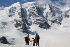 Tre personer håller ögonen på på schweiziska berg Royaltyfri Bild