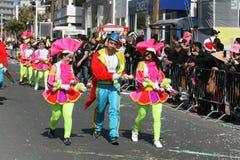 Tre personer i karnevaldräkter som marscherar längs en gata royaltyfria bilder