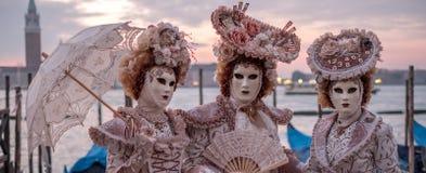 Tre personer i utsmyckade dräkter och maskeringar som framme står av Grand Canal i Venedig under karnevalet arkivbild
