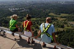 Tre personer sitter längs kanten av det Tallinn TVtornet royaltyfri foto