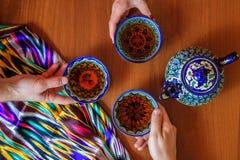 Tre personer som dricker te från pials Samarkand Uzbekistan orientalisk kokkonst Fotografering för Bildbyråer