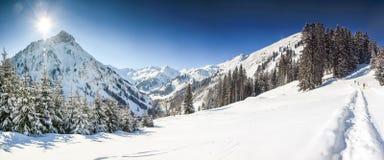 Tre personer som fotvandrar i berg, övervintrar landskap med djup snö på klar solig dag Allgau Bayern, Tyskland Arkivfoto