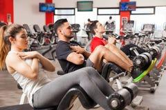Tre personer som gör knastranden i en idrottshall Arkivfoto