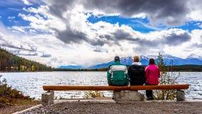 Tre personer som tycker om sikten av pyramid sjön i Jasper National Park Arkivbild