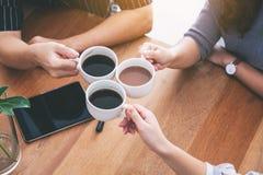 Tre personer tyckte om att dricka och att klirra kaffekoppar på trätabellen i kafé royaltyfri foto
