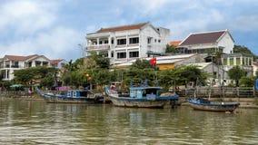 Tre pescherecci di legno lungo la banca di Thu Bon River in Hoi An, Vietnam, con l'hotel nei precedenti fotografie stock