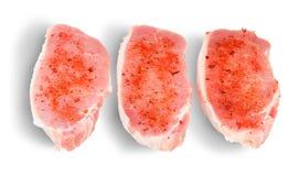 Tre pezzi di carne di maiale cruda con le spezie Fotografie Stock Libere da Diritti