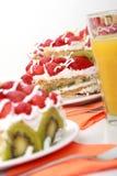 Tre pezzi di dolce casalingo è servito con succo d'arancia Fotografie Stock Libere da Diritti