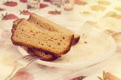 Tre pezzi di pane nero su un piatto di plastica con e sulle forcelle Fotografia Stock