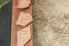 Tre pezzi di terraglie in una sabbiera immagini stock