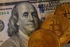 Tre pezzo-monete dell'oro sopra cento dollari di banconota isolata su fondo nero, cryptocurrency che accetta per il pagamento e immagini stock