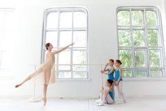 Tre piccole ballerine che ballano con l'insegnante personale di balletto nello studio di ballo immagini stock