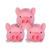 Tre piccole banche di moneta del maiale impilate su a vicenda Fotografie Stock