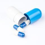 Tre piccole pillole stanno uscendo dalla grande capsula blu e bianca Fotografia Stock