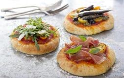 Tre piccole pizze con la sardina ed il prosciutto fotografia stock libera da diritti