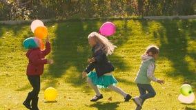 Tre piccole ragazze felici che gettano i loro palloni variopinti all'aria archivi video