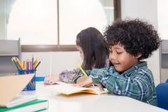 Tre piccoli bambini che si siedono la matita della tenuta della mano e l'immagine di coloritura Immagine Stock