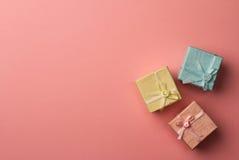 Tre piccoli contenitori di regalo con i nastri su fondo rosa Immagine Stock Libera da Diritti