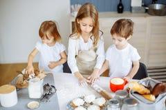 Tre piccoli cuochi unici che godono nella cucina che fa grande mess Bambini che producono i biscotti nella cucina fotografie stock libere da diritti
