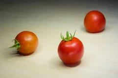 Tre piccoli pomodori rossi si trovano su un fondo di legno leggero Fotografia Stock