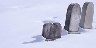 Tre pietre tombali in neve un giorno soleggiato immagini stock