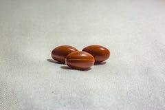 Tre pillole su un fondo bianco con tessuto strutturano il colpo in st Immagine Stock Libera da Diritti
