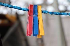 Tre pinnor som hunging på blått, tvinnar och att vänta på kläder Royaltyfria Bilder