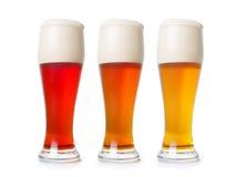Tre pinte differenti della birra su bianco con il percorso di residuo della potatura meccanica Fotografia Stock