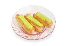Tre pistascheclairs på den rosa glass maträtten Royaltyfri Fotografi