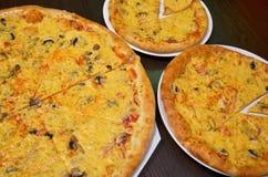 Tre pizza med ost och champinjoner av olika format på en mörk bakgrund royaltyfria bilder