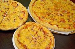 Tre pizza med ost och kött av olika format på en mörk bakgrund arkivfoton