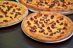 Tre pizza med ost och rökte korvar av olika format på en mörk bakgrund royaltyfri fotografi