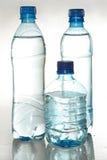 Tre plastic flaskor med potable vatten Fotografering för Bildbyråer