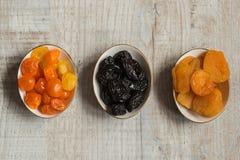 Tre plattor med torkade frukter på träbakgrund: torkade mandariner, katrinplommoner och torkade aprikors Royaltyfri Foto