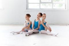 Tre poche ragazze di balletto che si siedono insieme e che posano fotografie stock libere da diritti