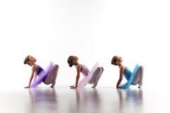 Tre poche ragazze di balletto che si siedono in tutu e che posano insieme fotografie stock
